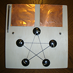 Square wood box with two copper plates and a pentagram connecting five knobs